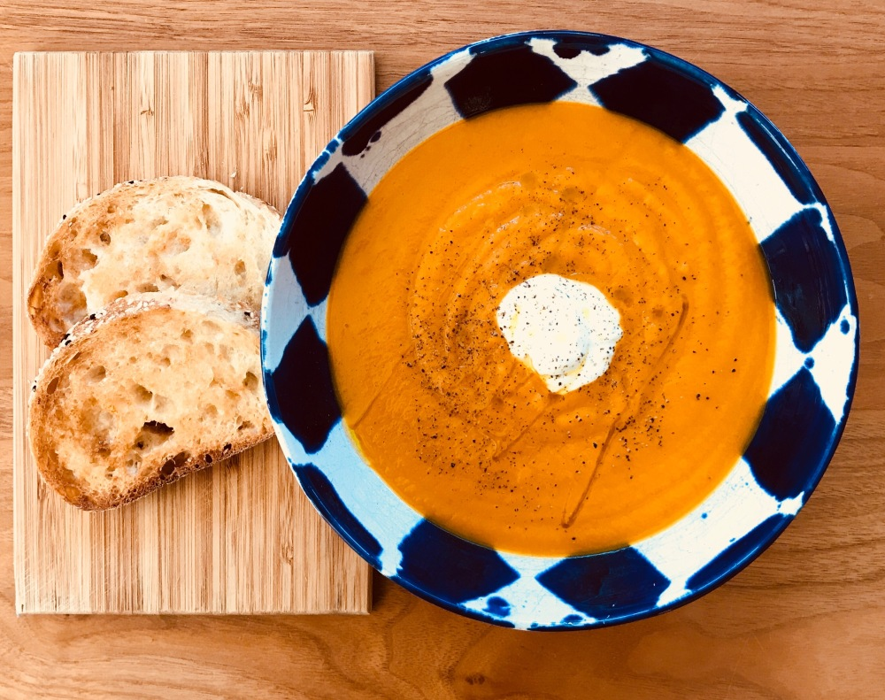 Pumpkin, sweet potato and carrot soup in bowl with toast on the side