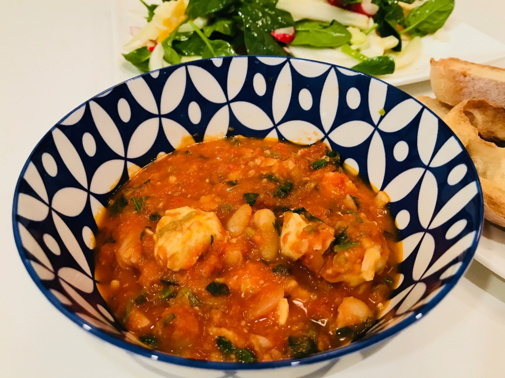 Seafood, tomato and cannellini bean stew in a bowl served with bread and salad
